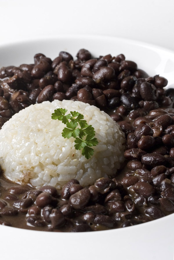 white rice accompained by black dry beans served in a plate with parsley decoration. vertical composition